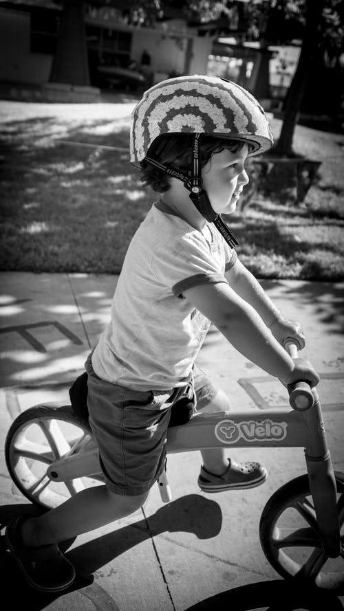 Free stock photo of balance bike, black and white, boy, helmet