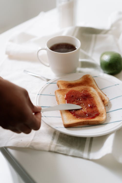 A Person Spreading Jam on Toast