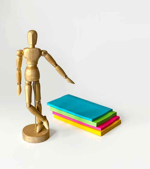Brown Wooden Human Figure on Blue Book