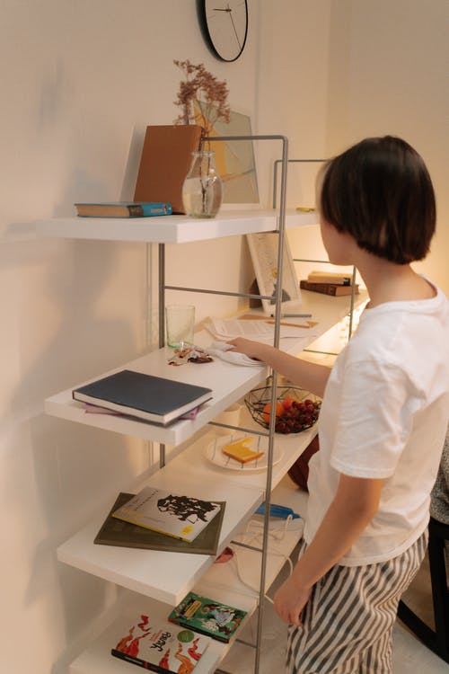 Woman in White Shirt Standing in Front of Table With Laptop Computer