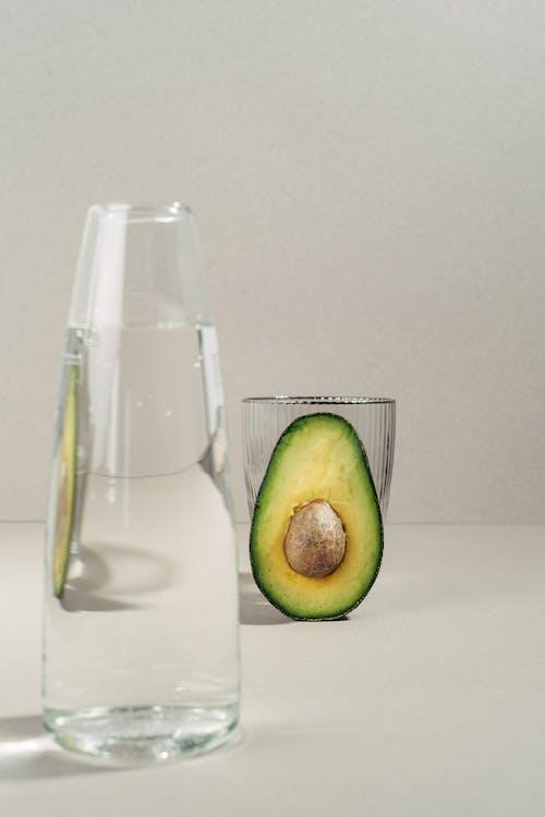 Green Apple Beside Clear Glass Bottle