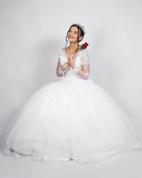 Full body of cheerful young bride in elegant white dress and tiara smiling while standing in light studio with red rose in hand