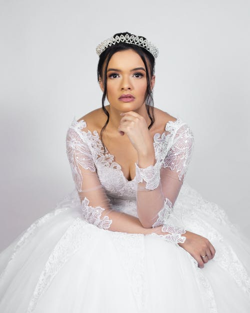 Elegant young woman in wedding dress sitting in white studio and looking at camera