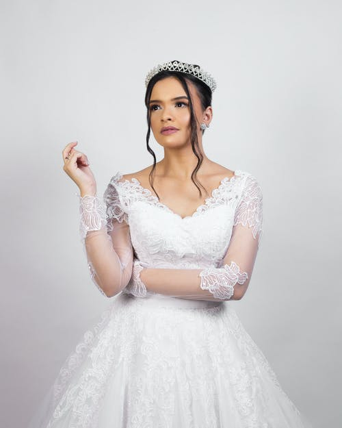 Elegant young bride in classy white dress and tiara standing in studio and looking away dreamily before wedding ceremony