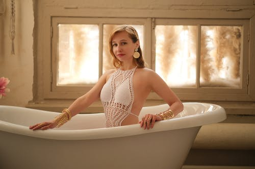 Smiling young redhead female wearing white underwear sitting in white bath and leaning on hands while looking at camera against window