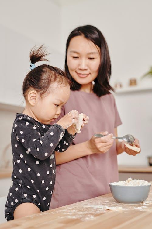 Girl in Black and White Polka Dot Long Sleeve Shirt Holding Dumplings