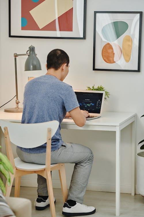Man in Blue Shirt Sitting on White Chair Using Macbook Air