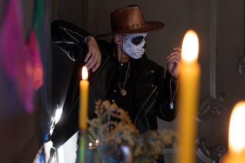 黑色外套控股点燃的蜡烛的女人