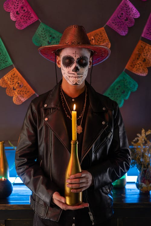 A Man with Face Paint Holding a Lighted Candle