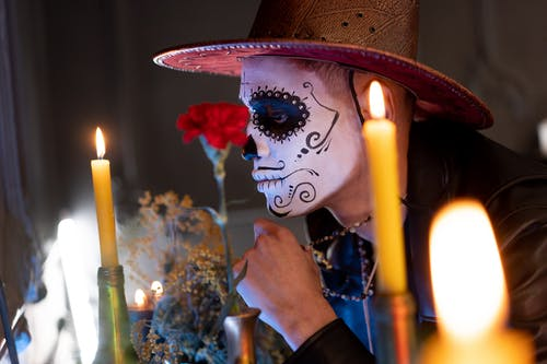A Man with Face Paint and Lighted Candles