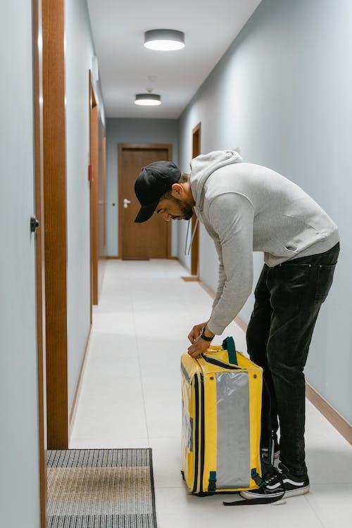 Man in Gray Sweater Standing In Front of a Door