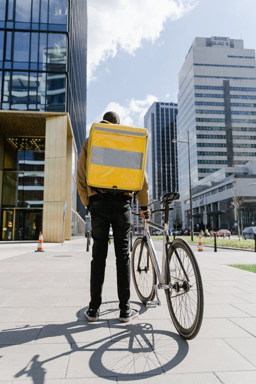 Man Carrying a Bag Standing Beside his Bicycle