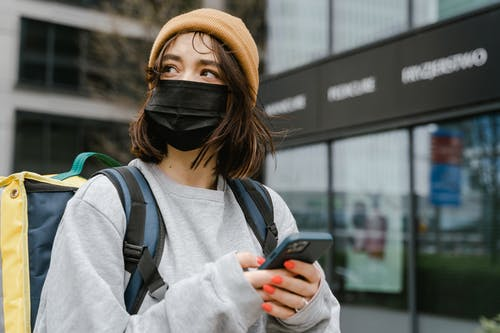 Woman in a Sweater and Beanie Holding a Smartphone
