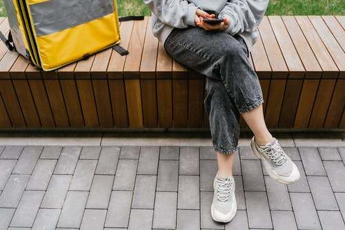 Person in Gray Sweater Sitting on a Bench