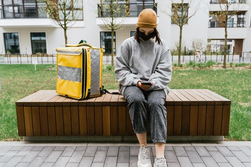 Woman in Gray Sweater Sitting on a Bench