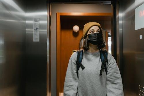 Woman in Gray Sweater in an Elevator