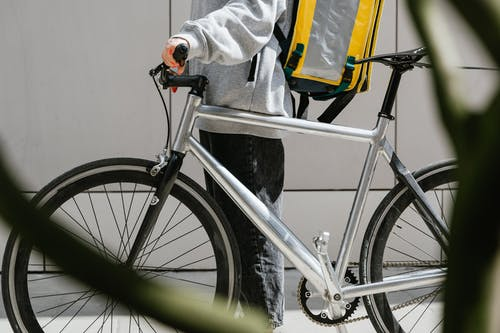Person in a Sweater Holding a Bicycle