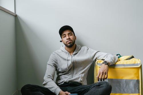 Man in Gray Hoodie Sitting on the Floor