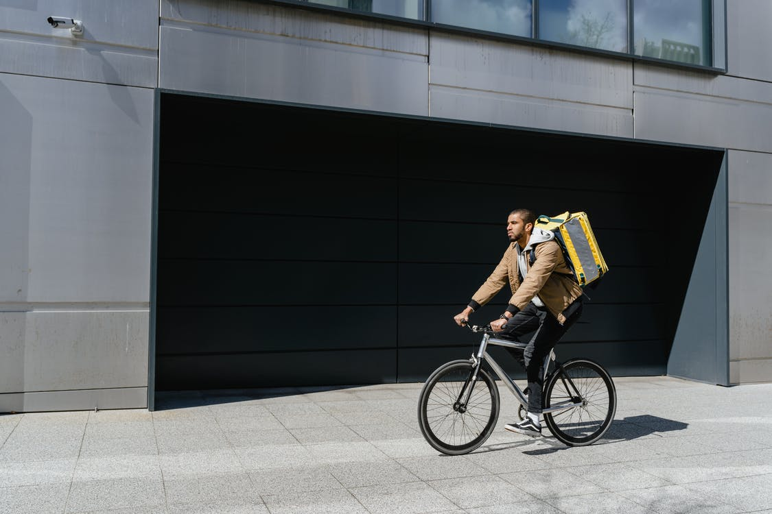 Man in Brown Jacket Riding a Bicycle