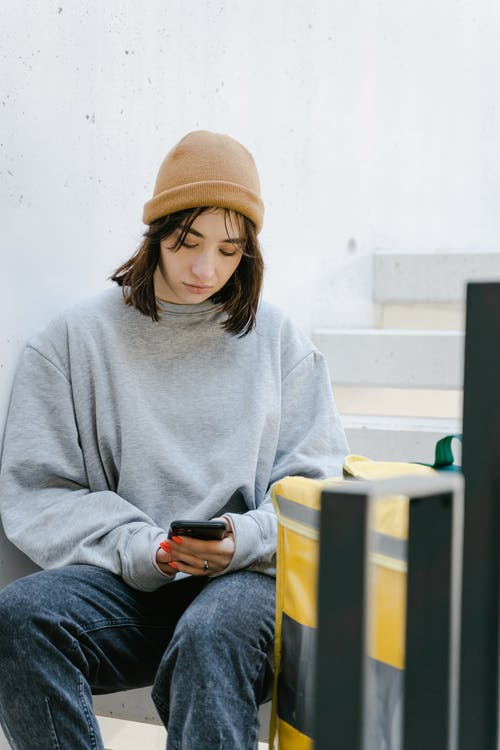 Woman in Gray Sweater and a Beanie Sitting on the Staircase