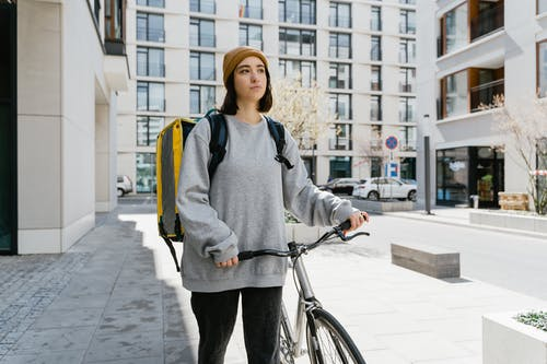 Woman in Gray Sweater and Black Pants Standing on Gray Concrete Pavement