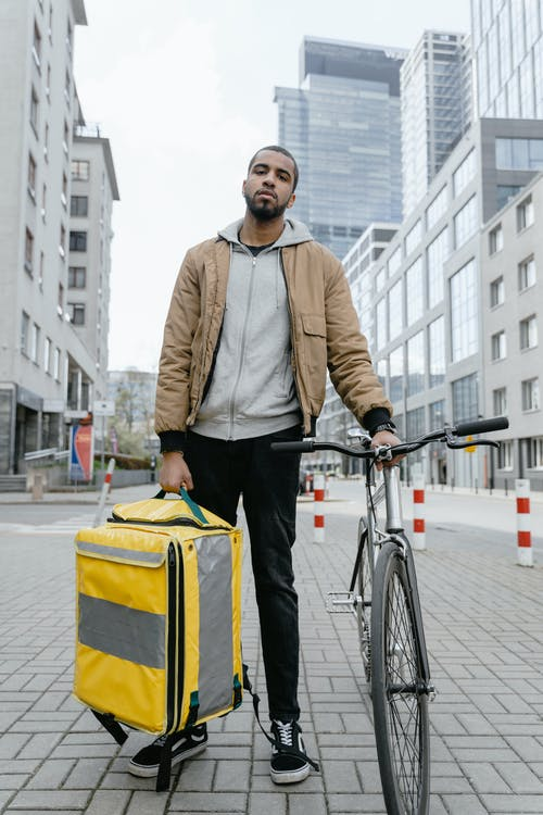 Man in Brown Zip Up Jacket and Black Pants Holding his Bicycle