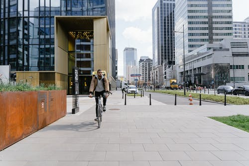 Man in Brown Jacket Riding a Bike