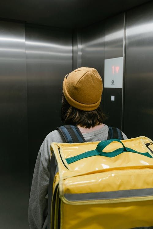 Woman in a Beanie Inside an Elevator