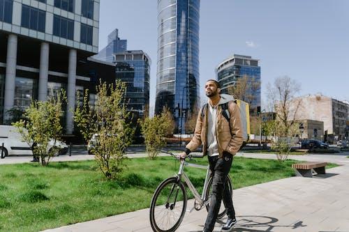 Man Wearing a Brown Jacket Walking on the Sidewalk