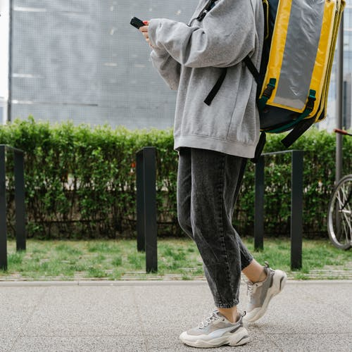 Person Carrying a Bag Walking on the Sidewalk