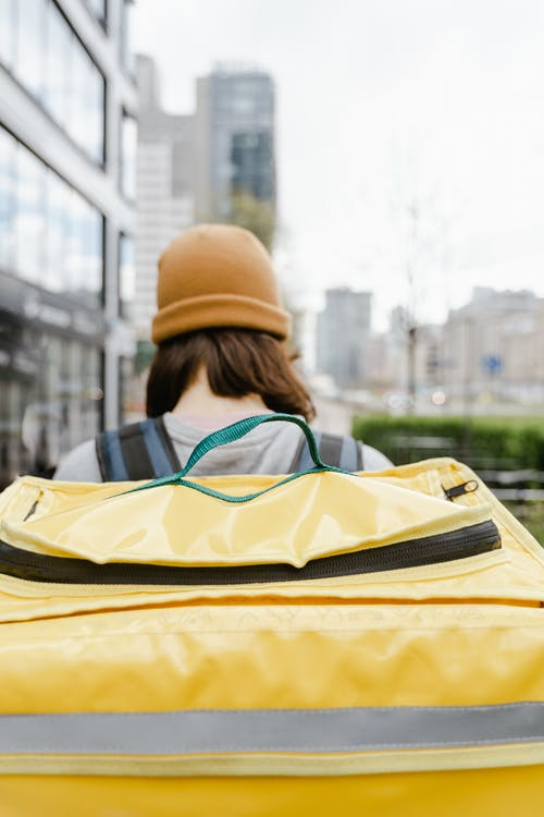 Person Wearing a Beanie Carrying a Yellow Bag