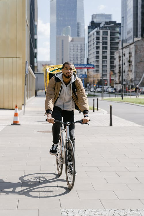 Man in Brown Jacket Riding a Bicycle on the Street