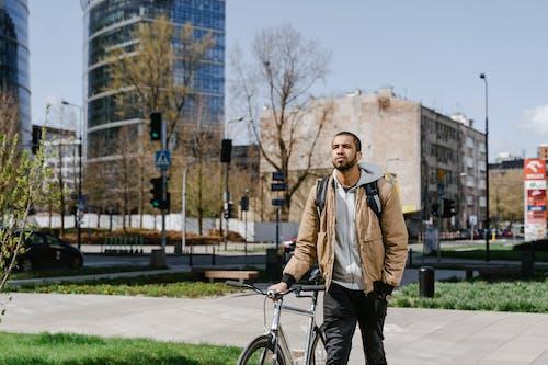 Man in Brown Jacket Standing on a Sidewalk