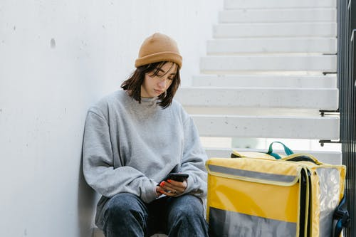 Woman in Gray Sweater and Blue Denim Jeans Sitting on the Staircase