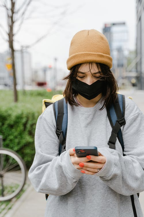 Woman Wearing a Face Mask Using a Mobile Phone