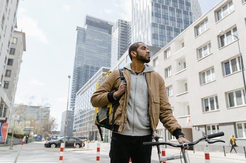 Man in Brown Jacket Standing on Road
