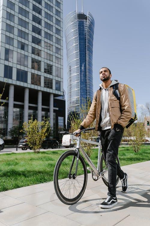 Man Walking while Holding his Bike