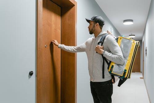 Deliveryman Knocking on a Door