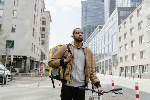 Man in Brown Jacket and Black Pants Standing on a Sidewalk