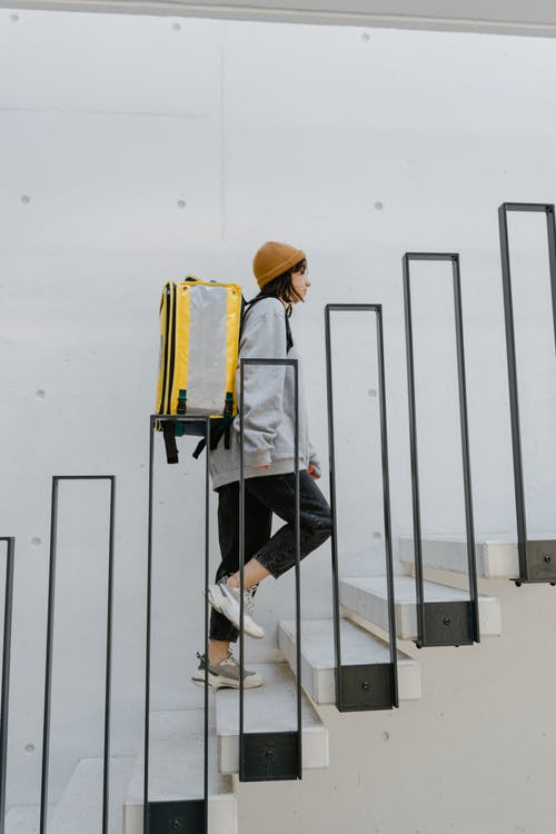 Man in White Long Sleeve Shirt and Black Pants Wearing Yellow Hard Hat Standing on Black