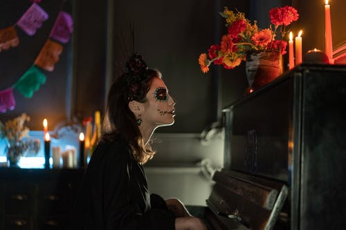 Woman with Skeleton Face Makeup Looking at Lighted Candles