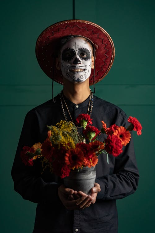 A Man with Face Paint Holding a Pot of Flowers