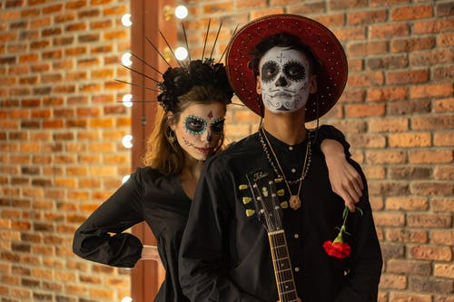 A Couple Wearing a Black Outfit and Face Paint