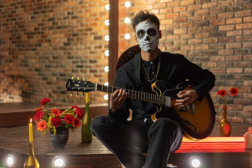 A Man with Face Paint Playing a Guitar