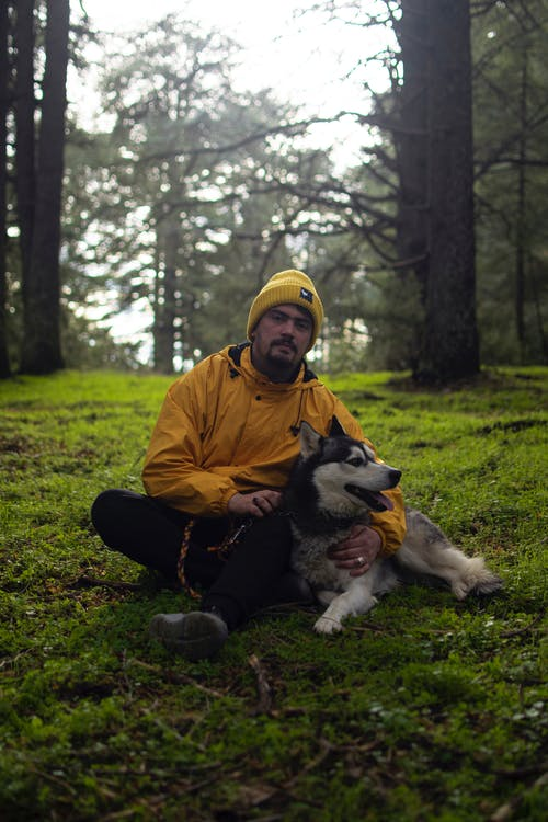 Man in Brown Jacket Sitting on Ground With Black and White Siberian Husky
