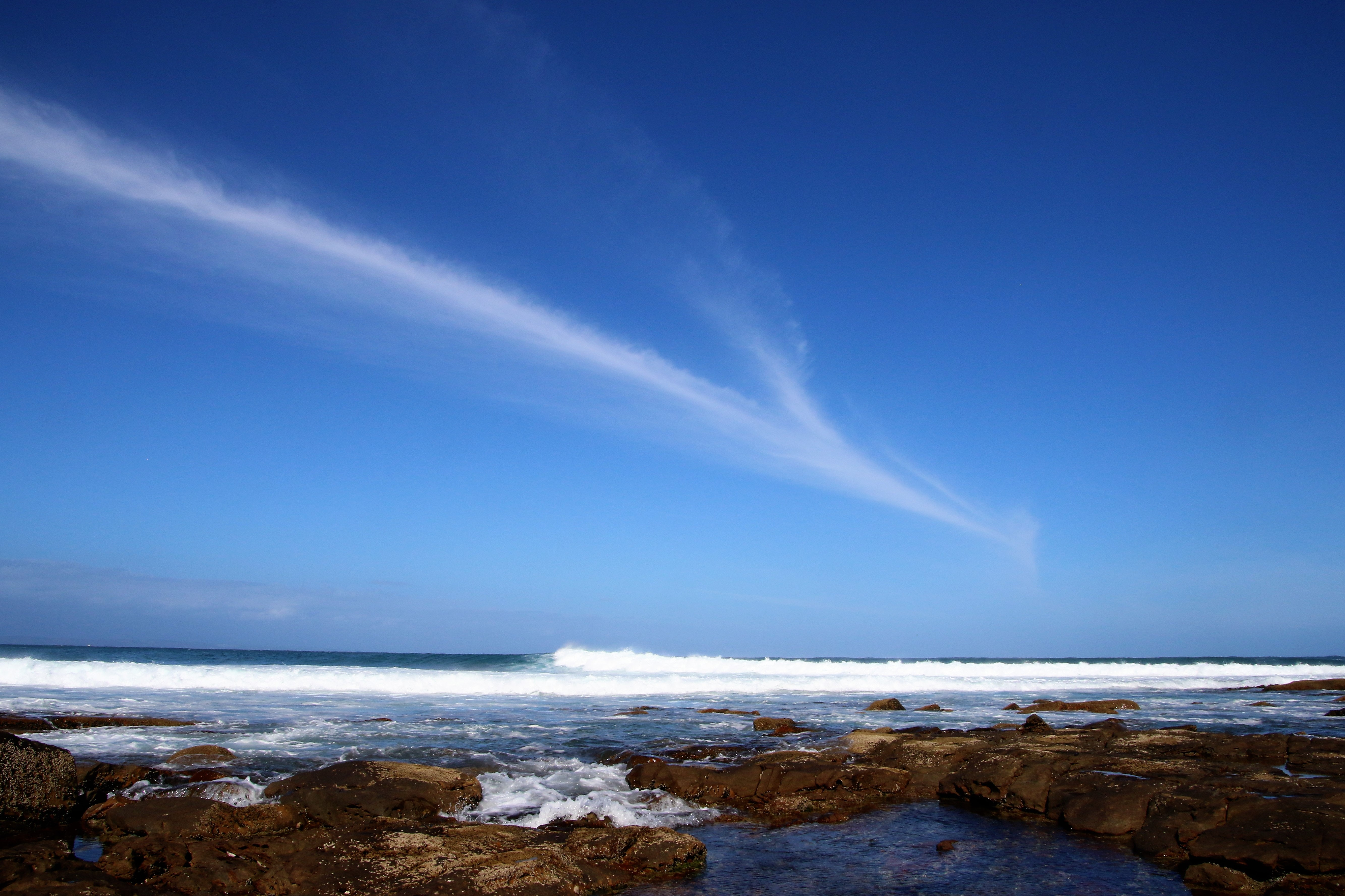 body of water under blue sky at daytime free stock photo