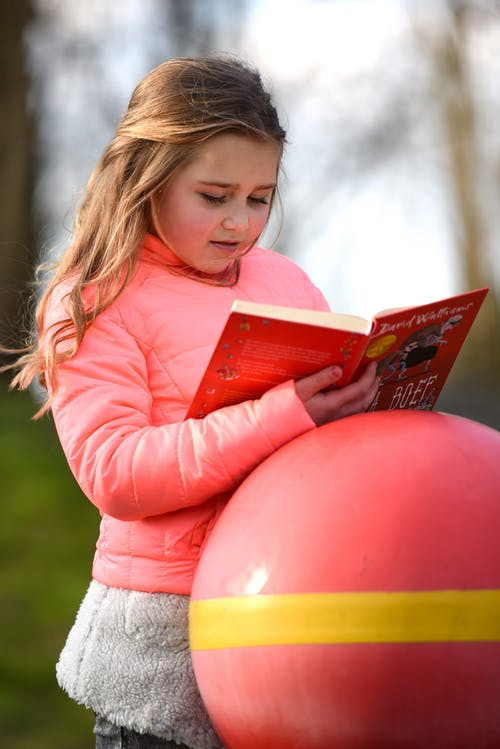 Girl in Pink Long Sleeve Shirt Holding Red Balloon