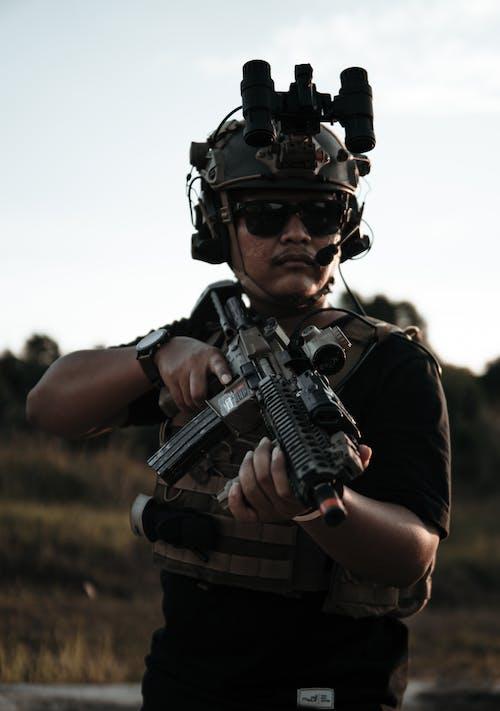 Man in Black Shirt Carrying Black Rifle