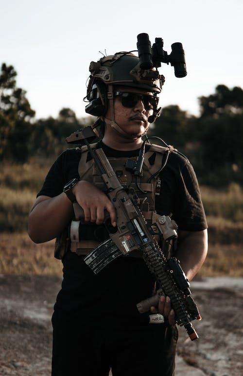 Man in Black Shirt Holding Rifle