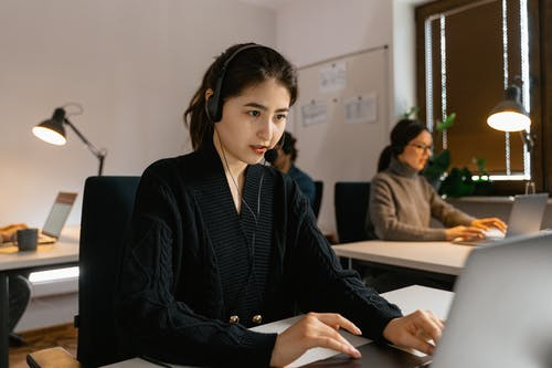 A Woman Wearing a Headset and Using a Laptop